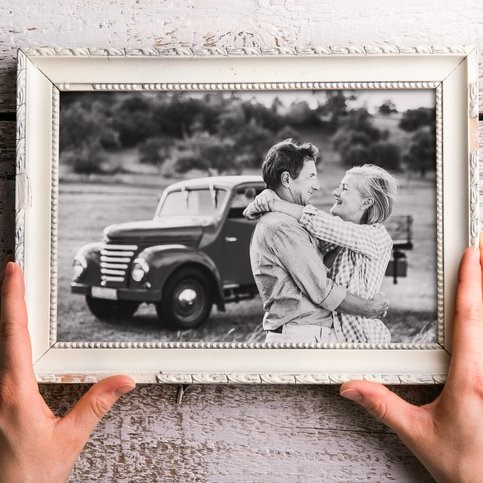 Hands holding picture frame of couple hugging in front of a vintage car