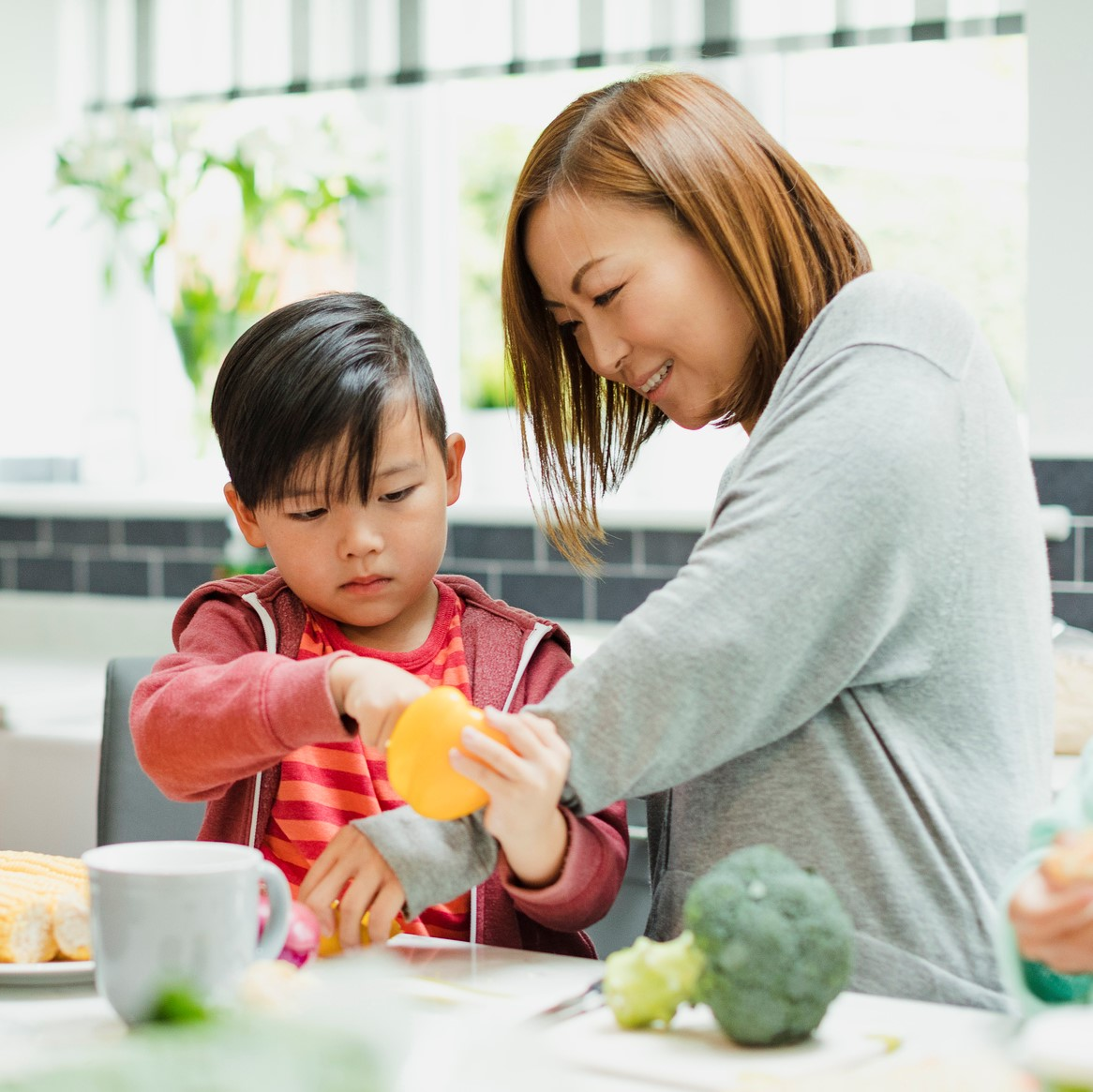 Family are preparing vegetables for dinner in the kitchen of their home. The mother is helping the little boy prepare a yellow bell pepper.