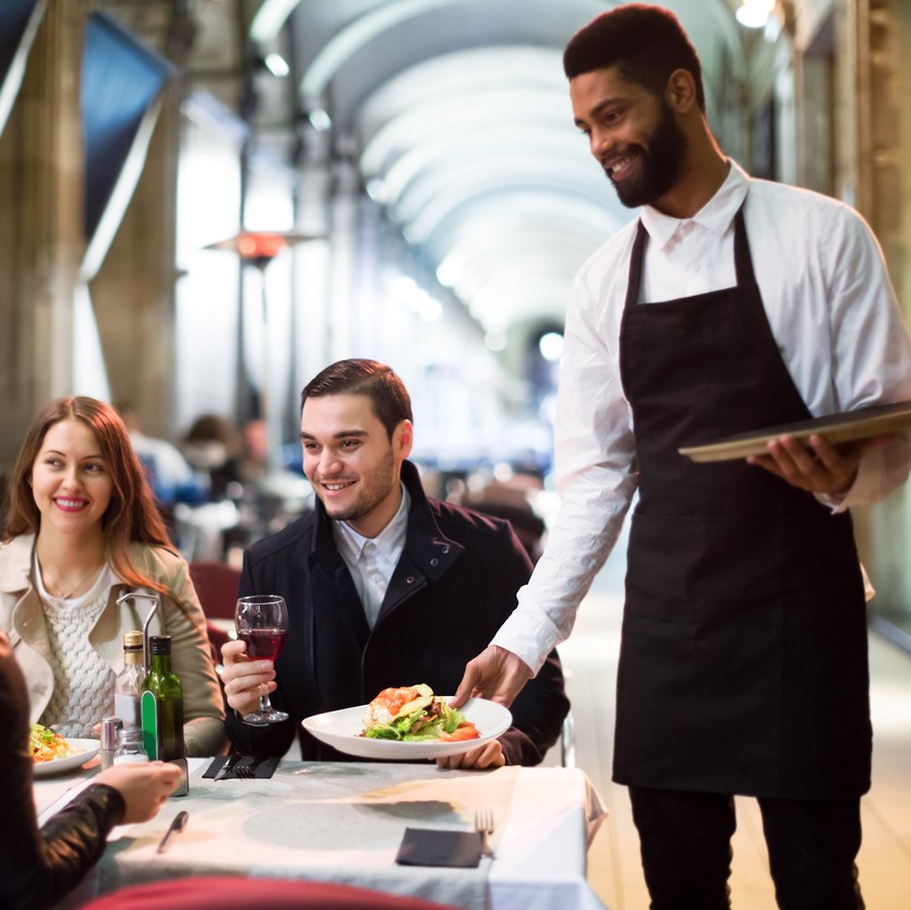Waiter serving restaurant guests at a table