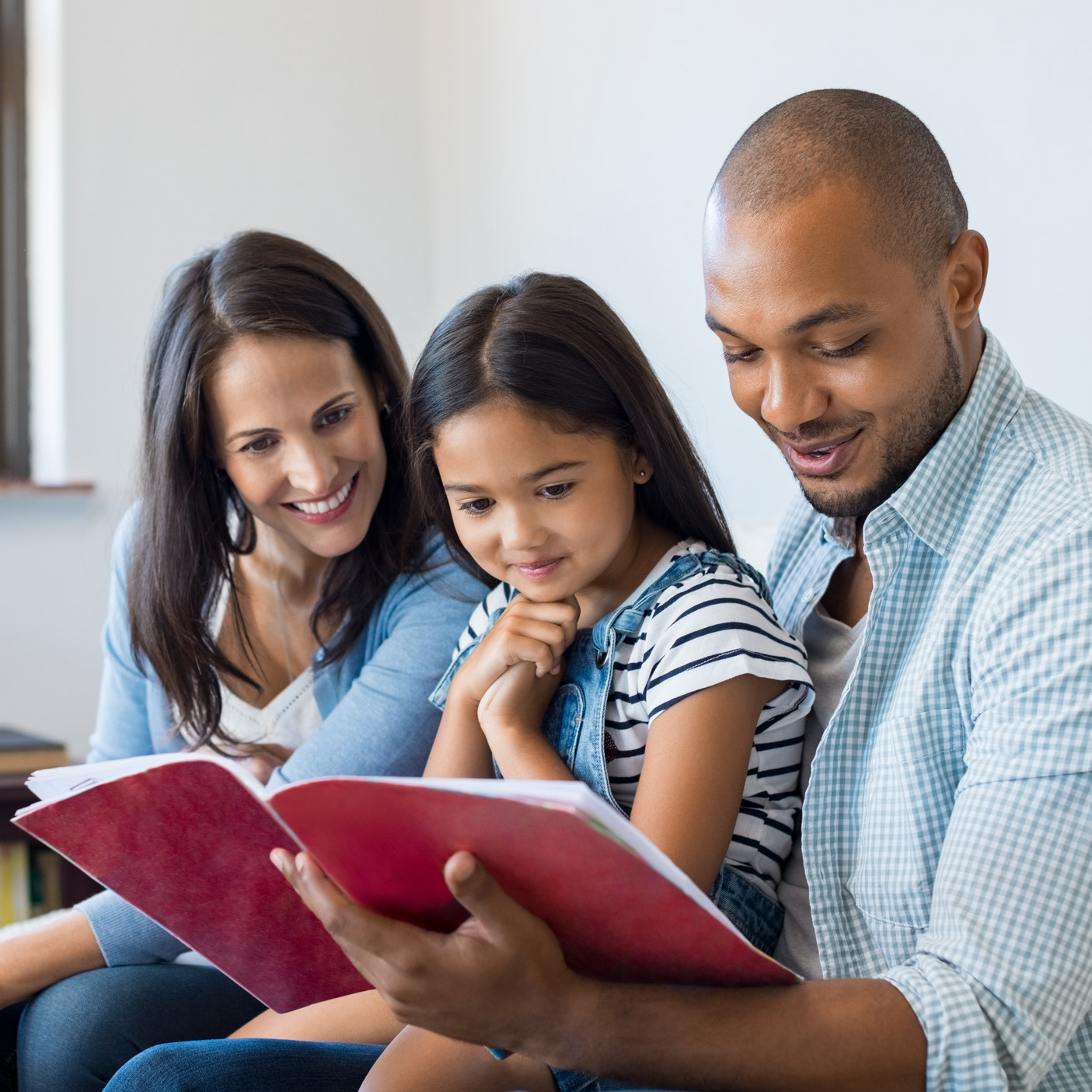 Happy multiethnic family sitting on sofa together looking at daughter's drawing book. African father reading the homework on exercise book of his cute kid. Parents feeling proud on progress of daughter.