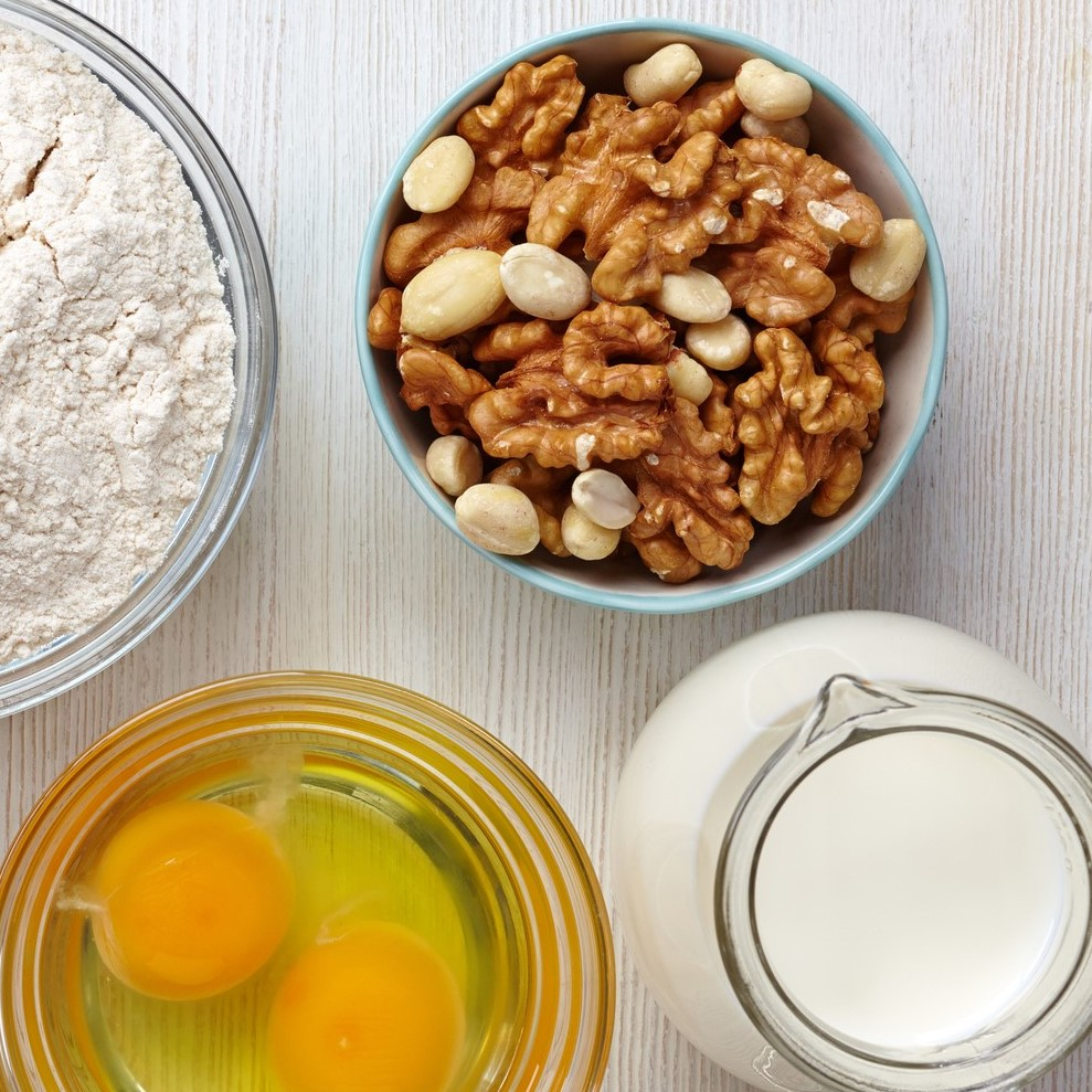 Egg, flour, milk, and tree nuts on wooden table.