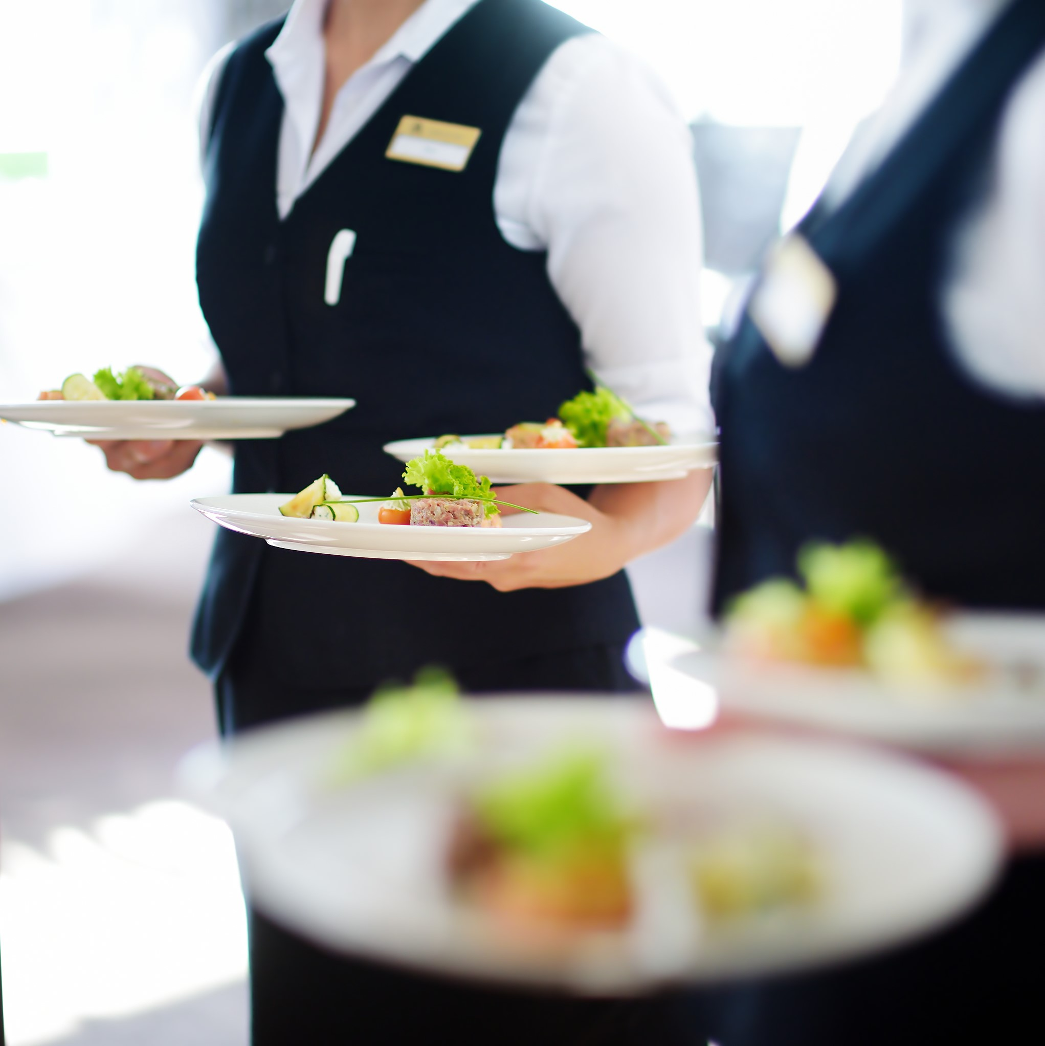 Waiter carrying plates with meat dish on some festive event, party or wedding reception